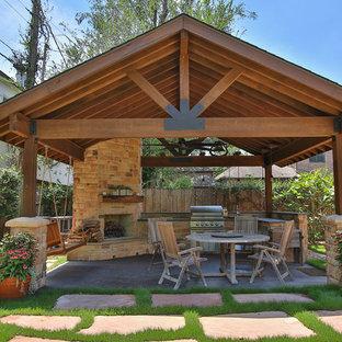 Großer Uriger Patio hinter dem Haus mit Outdoor-Küche, Gazebo und Betonplatten in Houston