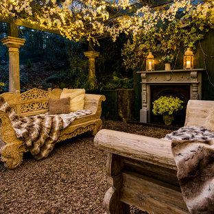 Idée de décoration pour une terrasse arrière style shabby chic de taille moyenne avec du gravier, un foyer extérieur et une pergola.