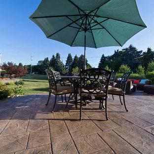 Esempio di un patio o portico tradizionale di medie dimensioni e dietro casa con cemento stampato