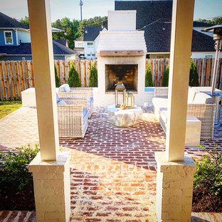 Ispirazione per un grande patio o portico stile shabby dietro casa con un caminetto e pavimentazioni in mattoni