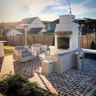 Immagine di un grande patio o portico shabby-chic style dietro casa con un caminetto e pavimentazioni in mattoni
