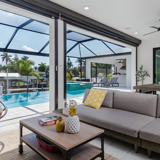 Inspiration for a contemporary backyard patio kitchen remodel in Miami with a roof extension