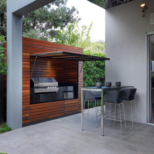 Large contemporary backyard patio in Melbourne with an outdoor kitchen, tile and a roof extension.