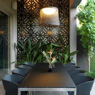 Ispirazione per un patio o portico design di medie dimensioni e dietro casa con un tetto a sbalzo e piastrelle
