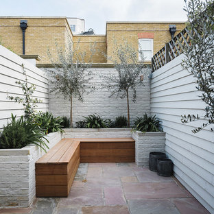 Contemporary back patio in London with no cover.