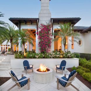 Ejemplo de patio exótico, grande, sin cubierta, en patio trasero, con brasero y adoquines de piedra natural