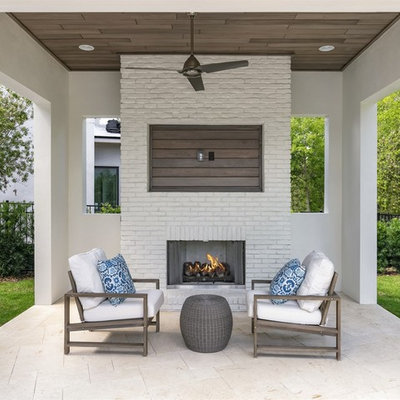 Inspiration for a mid-sized transitional backyard stone patio remodel in Orlando with a gazebo and a fireplace