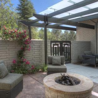 Ispirazione per un patio o portico boho chic di medie dimensioni e davanti casa con un focolare, pavimentazioni in cemento e una pergola