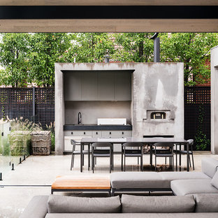 This is an example of a medium sized urban back patio in Melbourne with an outdoor kitchen, concrete slabs and an awning.
