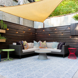 Inspiration for a small eclectic back patio in New York with a potted garden, concrete slabs and an awning.