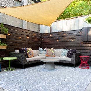 Ejemplo de patio ecléctico, pequeño, en patio trasero, con jardín de macetas, losas de hormigón y toldo
