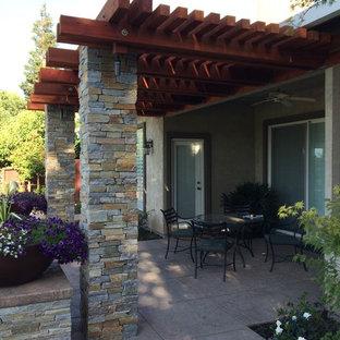 Immagine di un grande patio o portico chic dietro casa con cemento stampato e una pergola