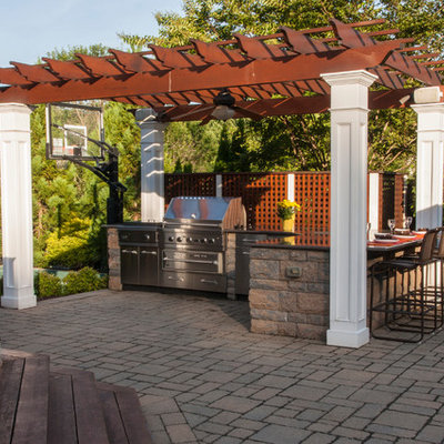 Inspiration for a mid-sized timeless backyard stone patio kitchen remodel in DC Metro with a pergola