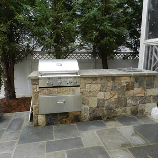 Example of a small 1950s backyard stone patio kitchen design in Raleigh with no cover