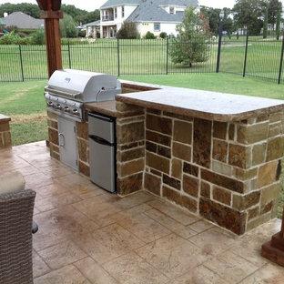 Immagine di un patio o portico american style dietro casa e di medie dimensioni con cemento stampato e un gazebo o capanno