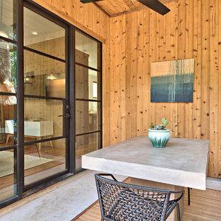 Ispirazione per un patio o portico country con lastre di cemento e un tetto a sbalzo