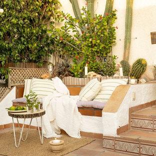 Imagen de patio mediterráneo, sin cubierta, con jardín de macetas y suelo de baldosas