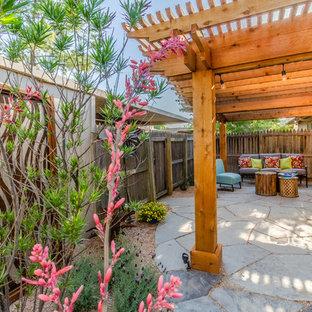 Patio - mid-sized southwestern backyard stone patio idea in Dallas with a pergola