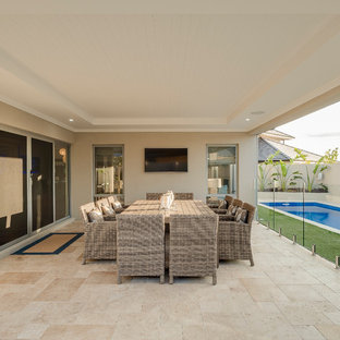 Photo of a contemporary backyard patio in Perth with natural stone pavers and a roof extension.