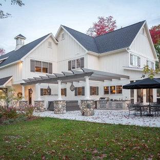 Immagine di un grande patio o portico classico dietro casa con lastre di cemento e una pergola