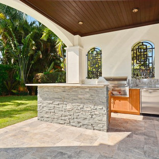 Design ideas for a medium sized mediterranean back patio in Miami with an outdoor kitchen, natural stone paving and a roof extension.