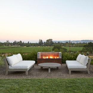 Immagine di un grande patio o portico country dietro casa con un focolare, ghiaia e nessuna copertura