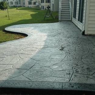 Ispirazione per un grande patio o portico classico dietro casa con un focolare, cemento stampato e nessuna copertura
