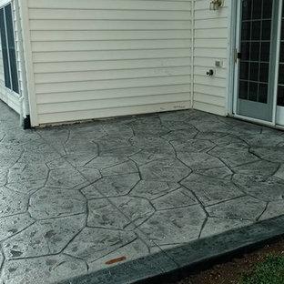 Immagine di un grande patio o portico tradizionale dietro casa con un focolare, cemento stampato e nessuna copertura