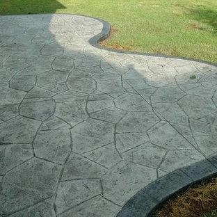 Ispirazione per un grande patio o portico chic dietro casa con un focolare, cemento stampato e nessuna copertura