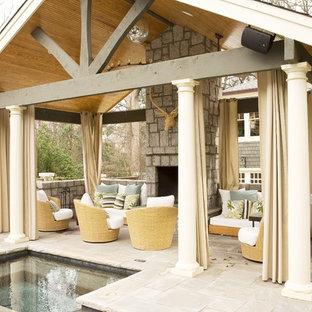 Foto di un patio o portico costiero dietro casa con un gazebo o capanno, un focolare e pavimentazioni in pietra naturale