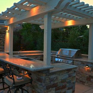 Ispirazione per un grande patio o portico stile americano dietro casa con pavimentazioni in cemento e una pergola