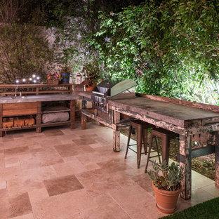 Foto di un patio o portico design di medie dimensioni e dietro casa con un focolare, piastrelle e una pergola