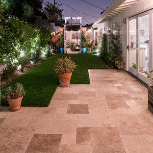 Idee per un patio o portico design di medie dimensioni e dietro casa con un focolare, piastrelle e una pergola
