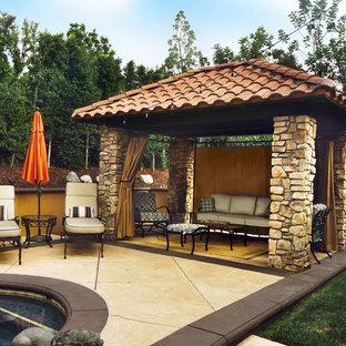 Esempio di un patio o portico mediterraneo di medie dimensioni e dietro casa con cemento stampato e un gazebo o capanno