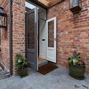 Idee per un grande patio o portico vittoriano in cortile con pavimentazioni in pietra naturale, una pergola e un giardino in vaso
