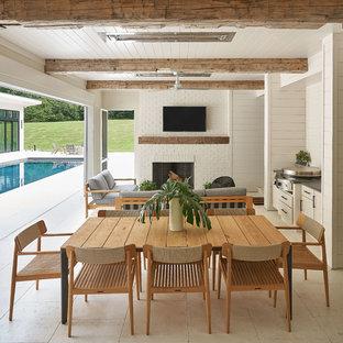 Ispirazione per un patio o portico chic con piastrelle e un tetto a sbalzo