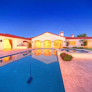 Foto di un grande patio o portico mediterraneo dietro casa con piastrelle e un tetto a sbalzo
