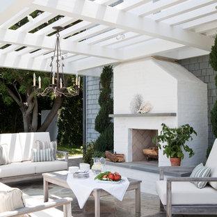 Patio - beach style stone patio idea in Los Angeles with a pergola