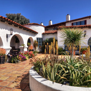 This is an example of an expansive mediterranean courtyard patio in Orange County with a water feature, tile and no cover.