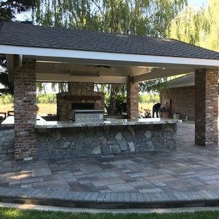 Foto di un patio o portico tradizionale di medie dimensioni e dietro casa con pavimentazioni in cemento e un tetto a sbalzo