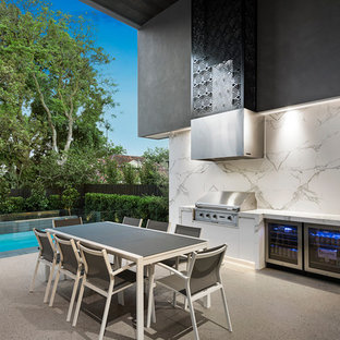 Photo of a large contemporary backyard patio in Melbourne with an outdoor kitchen, a roof extension and concrete slab.