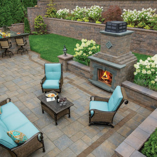 Large elegant backyard stamped concrete patio photo in Philadelphia with a fireplace and no cover