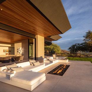 Idéer för mycket stora funkis uteplatser på baksidan av huset, med en öppen spis, betongplatta och takförlängning