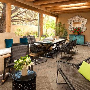 Cette image montre une terrasse avec une cuisine extérieure arrière sud-ouest américain de taille moyenne avec des pavés en pierre naturelle et une extension de toiture.