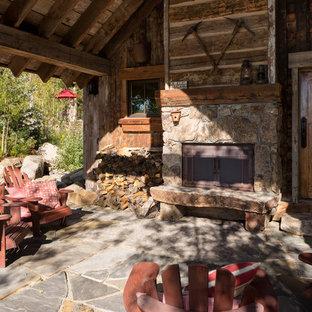 Immagine di un piccolo patio o portico rustico davanti casa con pavimentazioni in pietra naturale e un tetto a sbalzo