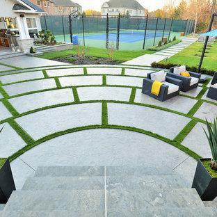 Foto di un grande patio o portico design dietro casa con lastre di cemento e un gazebo o capanno