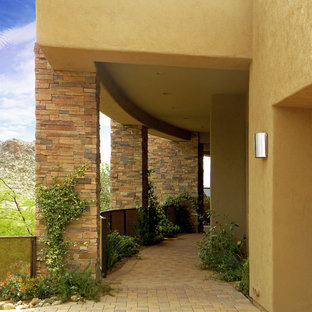 This is an example of a side yard patio in Other with a roof extension.