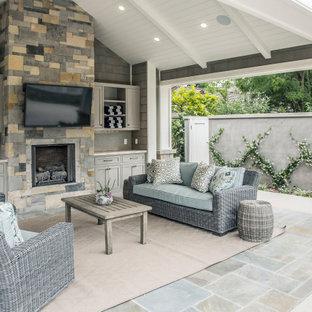 Immagine di un grande patio o portico classico dietro casa con piastrelle e un gazebo o capanno