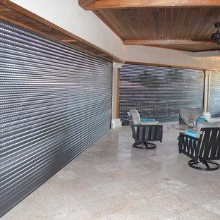 Foto di un grande patio o portico tropicale dietro casa con piastrelle e un tetto a sbalzo