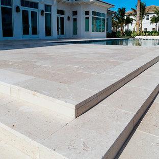 Foto di un patio o portico tropicale di medie dimensioni e dietro casa con pavimentazioni in pietra naturale e un gazebo o capanno